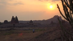 Girl walking from the Vittala Temple during sunset Stock Footage