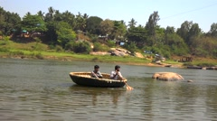 Two indian men in a boat at Tungabhadra river Stock Footage