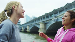 Female runners in the city chat together and high five Stock Footage
