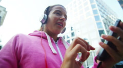 Female runner in the city with headphones and mobile phone Stock Footage