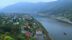 Village alongside river in mountains valley car traffic railroad, click for HD Stock Footage