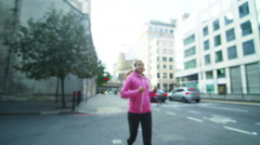 Female runner in the city with headphones and mobile phone - stock footage