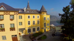 Yellow contemporary castle aerial, city town view, mountains, click for HD Stock Footage