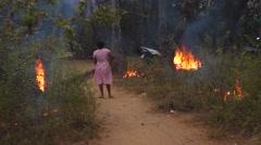 Woman burning rubbish near Palolem beach Stock Footage