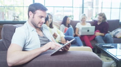 Attractive people socialise together whilst using technology - stock footage