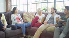Group of attractive friends socialise and laugh together. Stock Footage