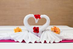 Stock Photo of white swans made from towels on bed in the hotel