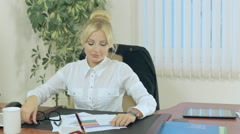 Attractive blonde wears glasses and signs documents and papers - stock footage