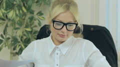 Attractive blonde takes off her glasses and leans back in her chair Stock Footage