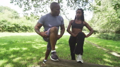 Man and woman doing stretching exercises in the park Stock Footage