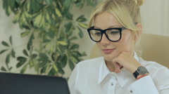 Girl smiling and looking at computer screen in office - stock footage
