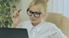 Nice girl smiling and looking at computer screen in office Stock Footage