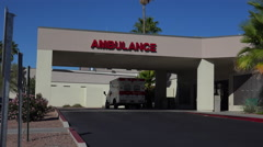 4K Hospital Ambulance Vehicle Parked Beneath Sign Outdoors Stock Footage