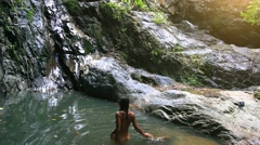 Nude sexy woman swims in a pond near waterfall. HD. 1920x1080 Stock Footage
