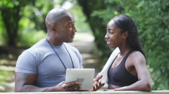 Portrait of sportswoman with personal trainer talking in the park.in slow motion - stock footage