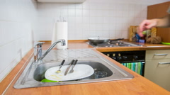 Cleaning kitchenware under water in kitchen Stock Footage