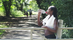 Athletic, sporty woman drinking a bottle of water in a park in slow motion Stock Footage
