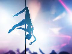 Woman performs pole dance in night club Stock Photos