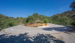 Worms eye view of hairpin bend curved road, ultra wide Stock Photos