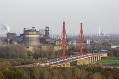 steel plant at the river rhine near duisburg, germany with the motorway bridg - stock photo