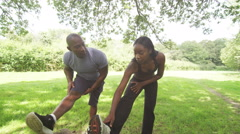 Man and woman doing stretching exercises in the park, slow motion Stock Footage