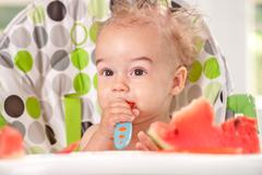Stock Photo of ragged baby holding spoon itself and eating watermelon