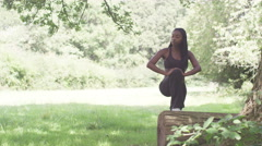 Sporty, young woman doing stretching exercises in the park - stock footage