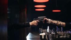 SLOW MOTION: Two male hands with guns take aim at each other. - stock footage