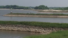 Groynes Waal River + pan downstream river bend and barges - wide shot. Stock Footage