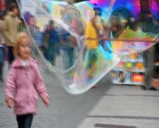 Children amazed by huge soap bubbles on the street, click for HD Stock Footage