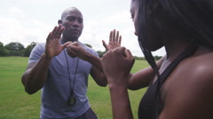 Young woman with trainer at boxing and self defense lesson outdoors. Slow motion - stock footage