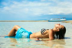 Sexy girl sunbathing in the water on the ocean Stock Photos