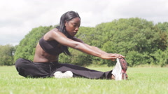 Young, sporty woman warms-up in the park in slow motion - stock footage