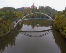 Aerial approaching 11-century castle up the river bridge, fall, click for HD Stock Footage
