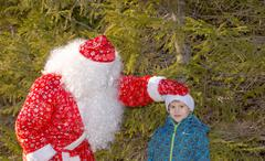 santa claus and the boy in wood near a fur-tree - stock photo