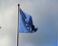 Stock Video Footage of Torn EU European Union flag, dark sky strong wind blowing, click for HD