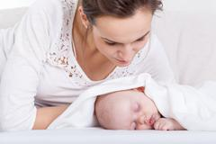 mother looking at her sleeping baby - stock photo