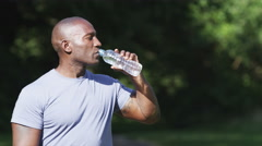 Portrait of athletic man drinking a bottle of water in a park in slow motion Stock Footage