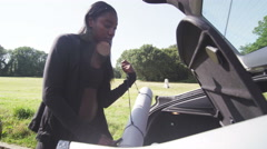 Young woman removes exercise equipment from car boot to prepare for workout. - stock footage