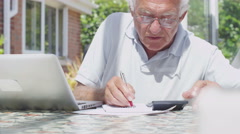 Senior gentleman at home doing the accounts and paying bills Stock Footage