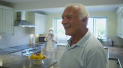 Portrait of happy senior gentleman in the kitchen at home - stock footage