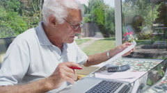 Senior gentleman at home doing the accounts and paying bills - stock footage