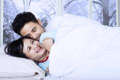 couple joking on bed in winter day - stock photo