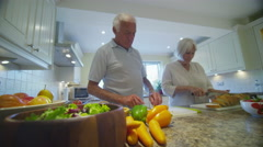 Affectionate senior couple preparing a meal together in the kitchen at home - stock footage