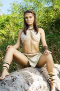 primitive woman sitting on a rock. amazon woman - stock photo