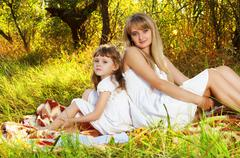 Mother and her child resting outdoors. holiday Stock Photos