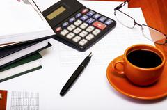 calculator,pen, notebook and business reports. coffee break - stock photo