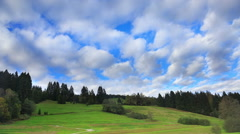 Fast cloud movement above green hill and forest, timelapse Stock Footage