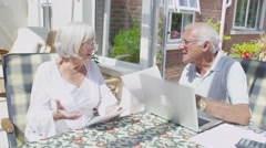 Senior couple together at home doing the accounts and worrying about paying bill Stock Footage