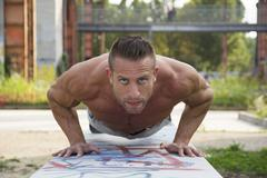 Handsome macho man shirtless in city park exercising, doing push-ups Stock Photos